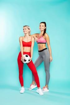Aimez le football sur toute la longueur de deux jeunes filles sportives attrayantes en tenue de sport tenant du football