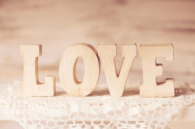 Aimez les lettres en bois sur le napperon au crochet, de style vintage
