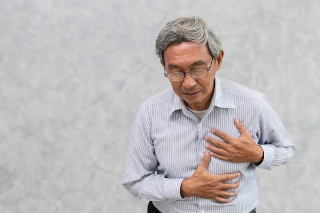 L'aîné asiatique souffre de la douleur de poitrine d'attaque cardiaque ou d'accident vasculaire cérébral avec l'espace pour le texte.
