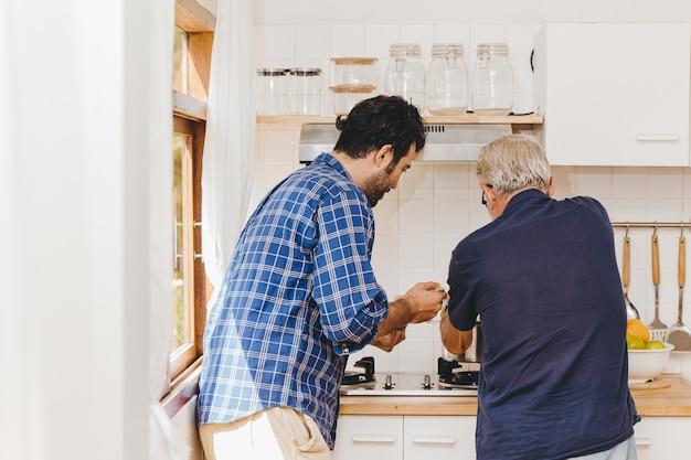 Un aîné cuisine dans la cuisine avec un jeune homme de la famille pour une activité à la maison ensemble.