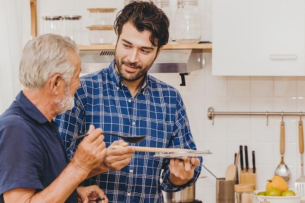 Un aîné goûte la nourriture tout en cuisinant dans la cuisine avec un jeune homme de la famille pour une activité à la maison ensemble.