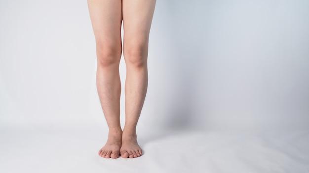 Aine et jambe mâles asiatiques et pieds nus sur fond blanc.