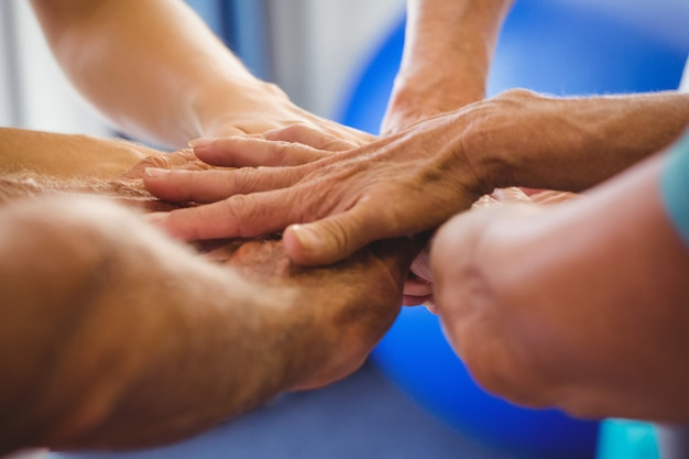 Les aînés et l'instructeur de conditionnement physique mettent leurs mains ensemble