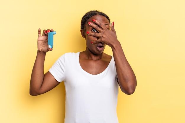L'air choqué, effrayé ou terrifié, couvrant le visage avec la main et regardant entre les doigts. notion d'asthme