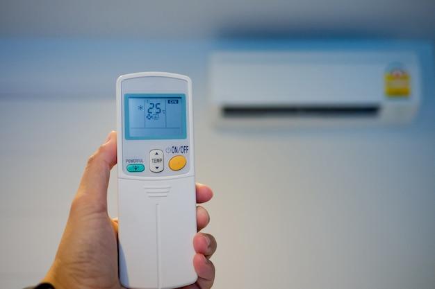 Air climatisé télécommandé sous la main, enregistrer le concept d'alimentation