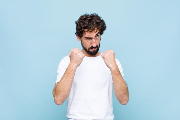 L'air confiant, en colère, fort et agressif, avec les poings prêts à se battre en position de boxe