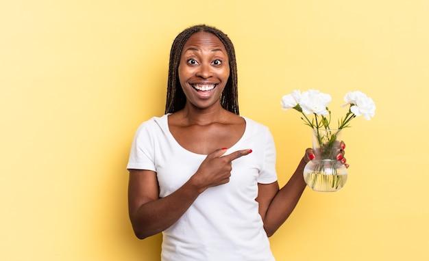 L'air excité et surpris en pointant sur le côté et vers le haut pour copier l'espace. concept de fleurs décoratives