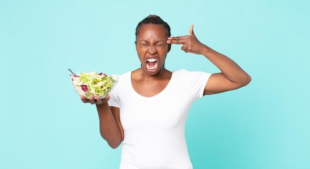 L'air malheureux et stressé, geste de suicide faisant un signe d'arme à feu et tenant une salade