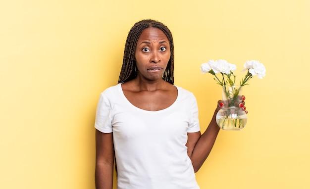 L'air perplexe et confus, mordant la lèvre avec un geste nerveux, ne connaissant pas la réponse au problème. concept de fleurs décoratives