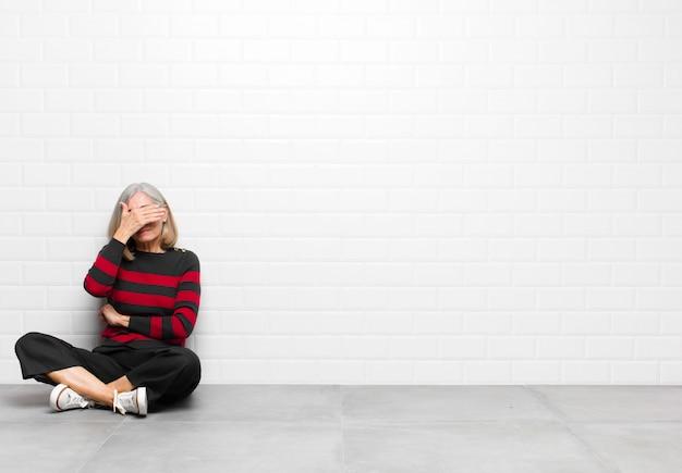 Air stressé, honteux ou bouleversé, avec un mal de tête, couvrant le visage avec la main