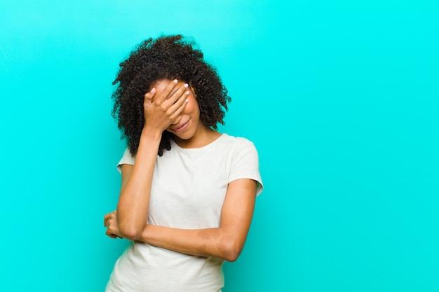 L'air stressé, honteux ou bouleversé, avec un mal de tête, couvrant le visage avec la main