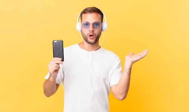 L'air surpris et choqué, la mâchoire baissée tenant un objet, écoutant de la musique avec des écouteurs et un smartphone