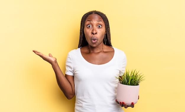 L'air surpris et choqué, la mâchoire baissée tenant un objet avec une main ouverte sur le côté tenant un pot de plante