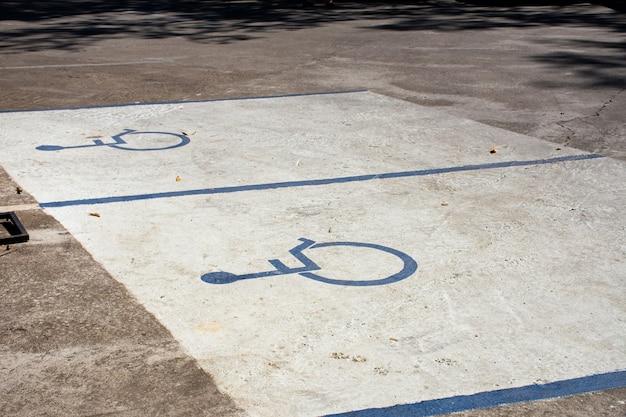 Aire de stationnement pour handicapés sur parking en béton.