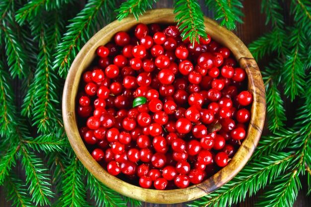 Airelle rouge, myrtille, canneberge, airelle dans un bol en bois sur une table en bois marron.