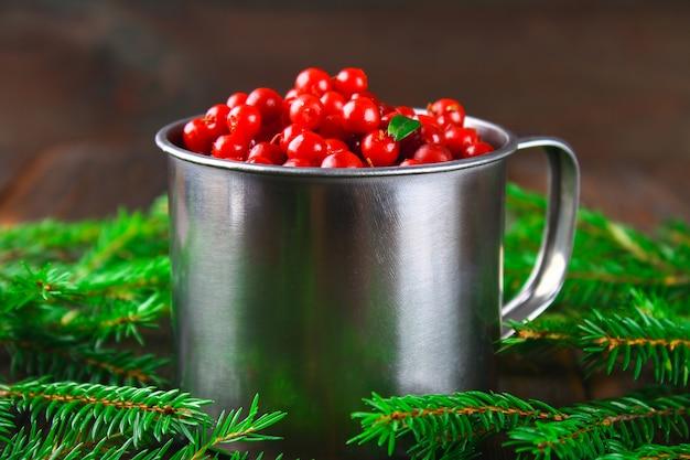 Airelle rouge, myrtille, canneberge, airelle dans une tasse en aluminium sur une table en bois marron.