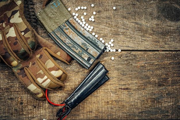Airsoft gun magazine et balles airsoft sur surface en bois