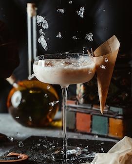Ajout de glaçons dans un verre à cocktail de noix de coco
