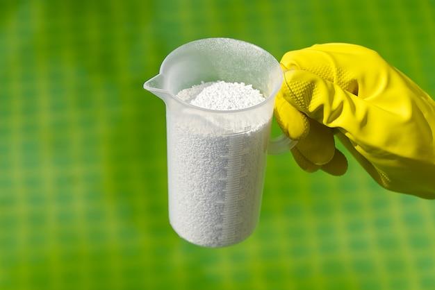 Ajout de poudre de chlore pour la piscine pour éliminer les algues et désinfecter l'eau.