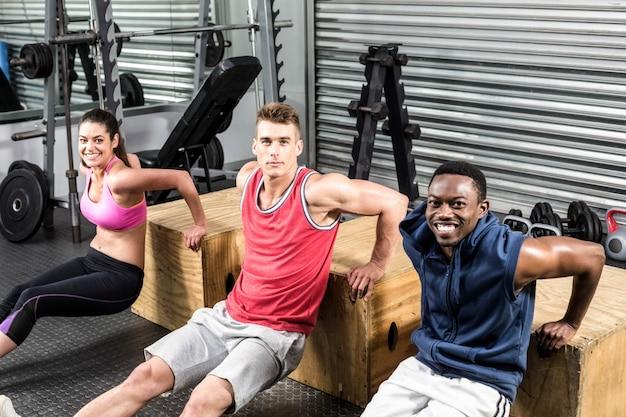 Ajustement des personnes faisant de l'exercice ensemble au gymnase de crossfit
