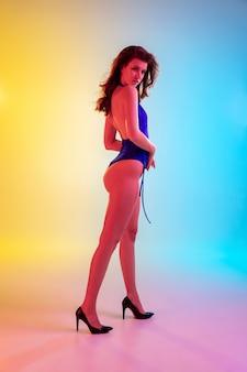 Ajuster. belle fille séduisante en maillot de bain bleu à la mode sur fond jaune-bleu dégradé en néon. portrait en pied. copyspace pour l'annonce. concept d'été, de mode, de beauté, d'émotions.