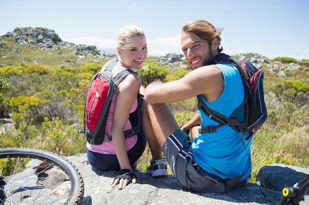 Ajuster le couple cycliste prenant une pause sur le pic rocheux, souriant à la caméra