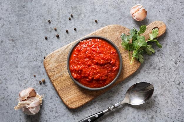 Ajvar savoureux. sauce végétale ou caviar de poivron rouge au four sur fond gris. cuisine balkanique.
