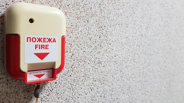Une Alarme Incendie Est Installée Sur Le Mur Du Bâtiment. L'inscription Feu Sur Le Sujet En Ukrainien Et En Anglais. Photo Premium