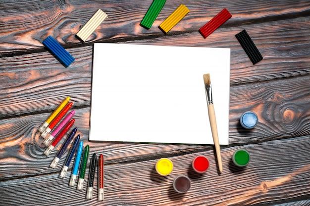 Album de dessin, pinceau, crayons de cire, peintures au doigt, pâte à modeler, fond rustique