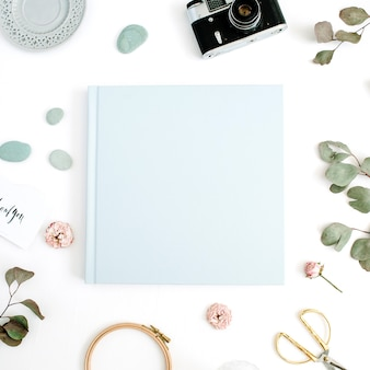 Album photo de famille ou de mariage bleu feuille d'eucalyptus, appareil photo rétro et boutons de rose secs sur blanc
