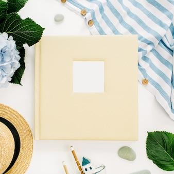 Album photo de mariage familial, bouquet de fleurs d'hortensia, couverture rayée, chapeau de paille sur surface blanche