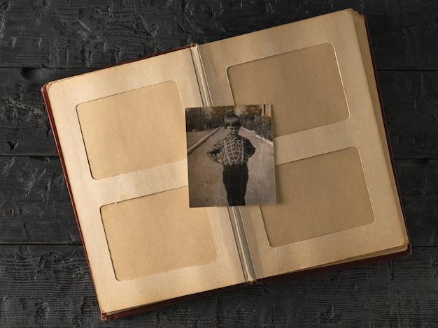 Un album photo ouvert avec une photo d'un garçon sur une table en bois. ancienne photo élégante. histoire.