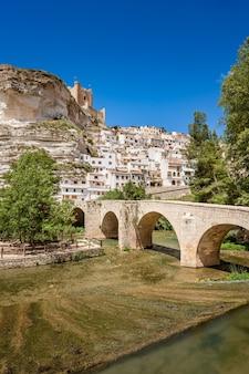 Alcala del jucar espagne village blanc avec un pont de pierre au-dessus d'une rivière