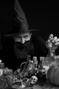 Un Alchimiste Mage Masculin Prépare Une Potion Pour Les Fêtes D'halloween Photo Premium