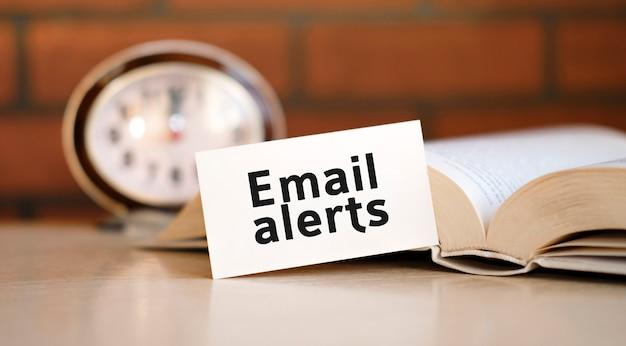 Alerte par e-mail - texte concept sur fond blanc avec une horloge et un livre ouvert
