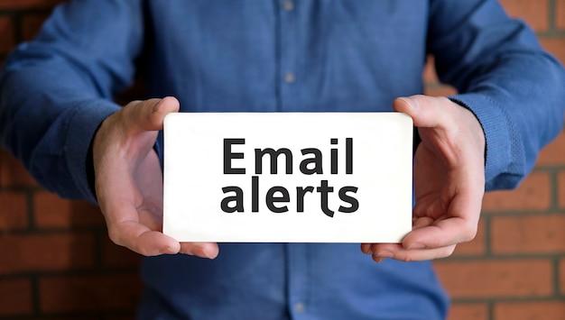 Alertes par e-mail - concept de référencement entre les mains d'un jeune homme en chemise bleue