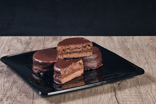 Alfajor au chocolat sur plaque noire sur une table en bois et fond sombre. mise au point sélective. copier l'espace