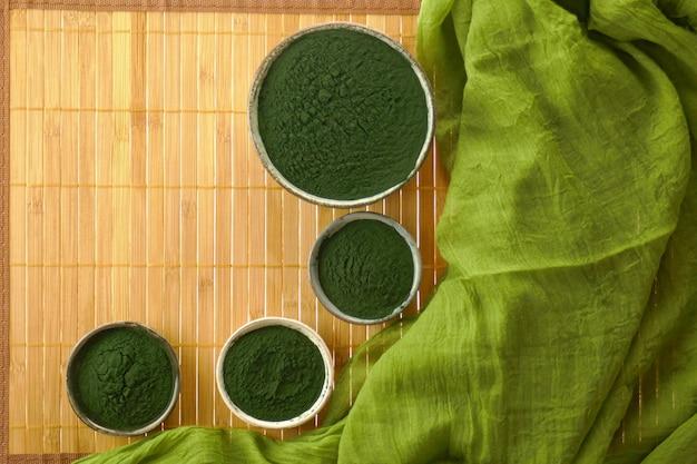 Algues spiruline, poudre de spiruline dans des tasses en céramique posées sur une natte de bambou