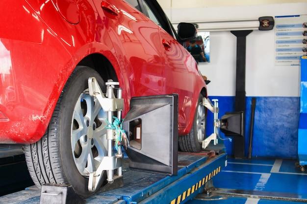 Alignement des roues de voiture en cours au centre de service de réparation automobile