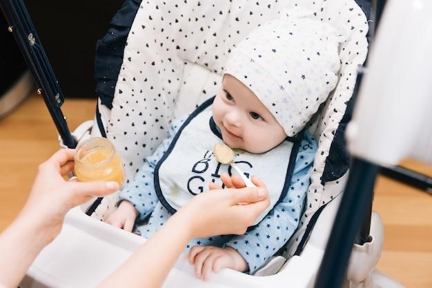 Alimentation. adorable bébé enfant mangeant avec une cuillère en chaise haute. bébé