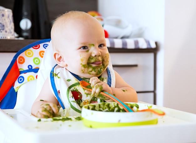 Alimentation adorable bébé enfant mangeant avec une cuillère dans une chaise haute babys premier aliment solide