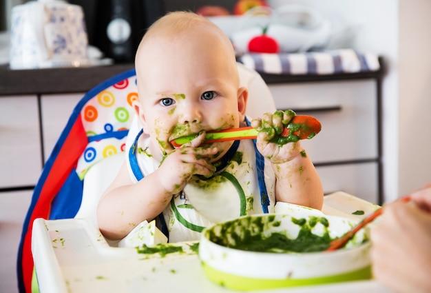 Alimentation. adorable bébé enfant mangeant avec une cuillère dans une chaise haute. le premier aliment solide de bébé