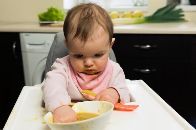 Alimentation. adorable bébé enfant mangeant avec une cuillère dans une chaise pour enfants. premier aliment solide pour bébé.
