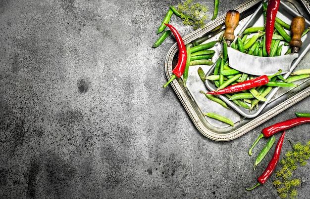 Alimentation biologique. pois verts, tomates et piment fort sur un plateau en acier. sur un fond rustique.