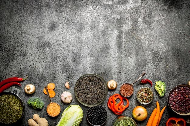 Alimentation biologique. une variété de légumineuses aux légumes. sur fond rustique.