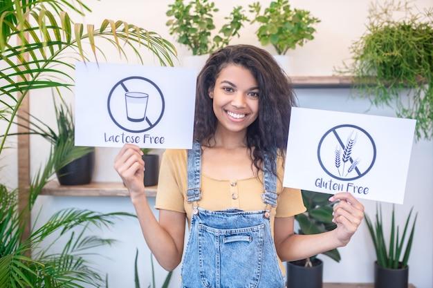 Alimentation équilibrée. souriante jeune femme mulâtre à la recherche montrant des affiches sans gluten sans lactose debout à l'intérieur