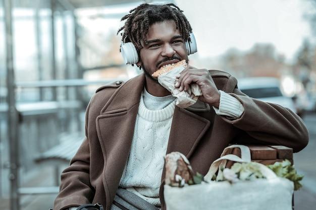 L'alimentation de rue. gentil homme brune portant des écouteurs tout en écoutant de la musique