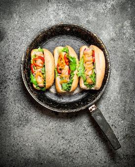 L'alimentation de rue. hot-dogs aux herbes et légumes dans la poêle sur table rustique.