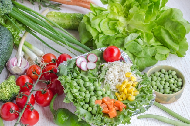 Une alimentation saine dans un sac en papier de différents légumes sur blanc. vue de dessus