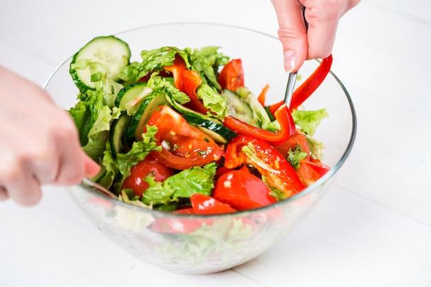 Alimentation saine, nourriture végétarienne, régime et concept de personnes - gros plan d'une jeune femme s'habillant d'une salade de légumes avec de l'huile d'olive sur fond blanc